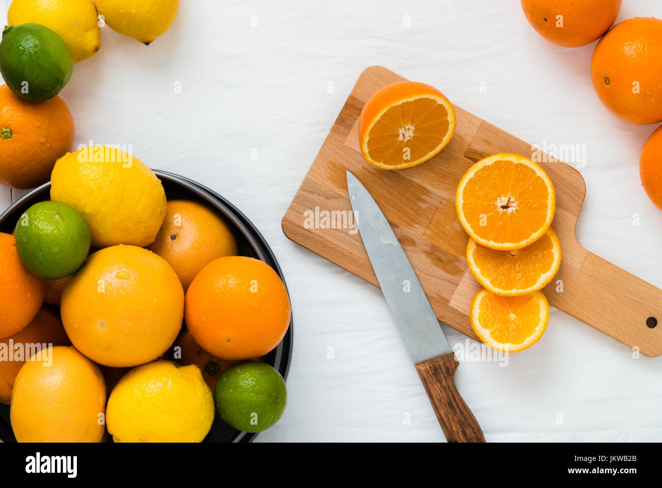 Bowl with different types of whole citruses: oranges, grapefruits, limes and lemons, and wooden board with slices - Stock Image