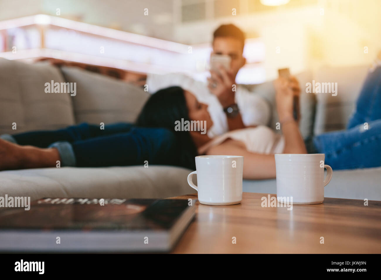 Two coffee cups on table with couple relaxing in background on couch. Cups of coffee in front with man and woman - Stock Image