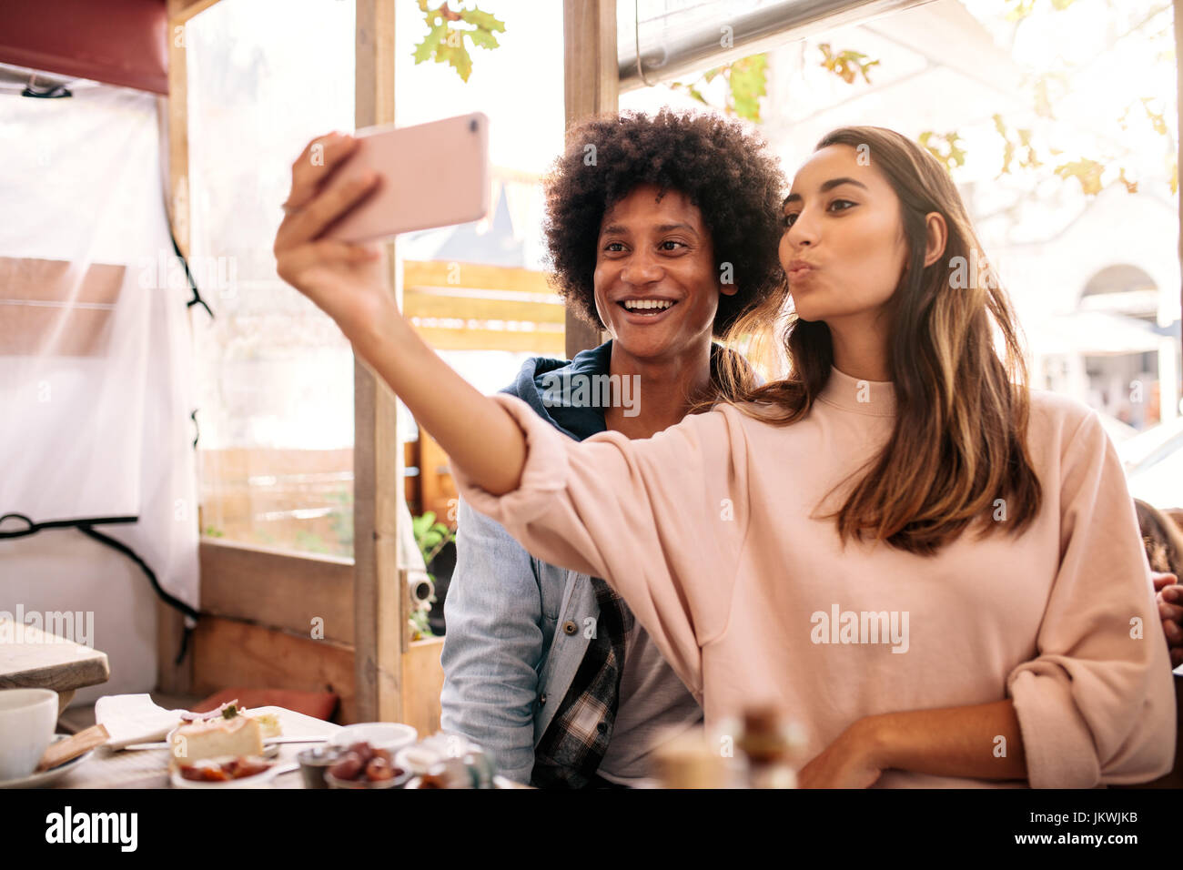 Young woman taking selfie with african man in cafeteria. Young couple looking at  smart phone in cafe. - Stock Image