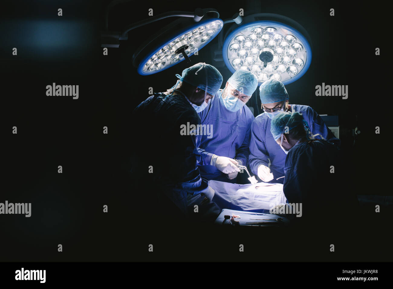 Group of surgeons in hospital operating theater. Medical team performing surgery in operation room. - Stock Image