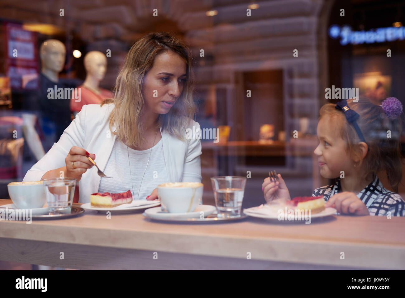 Young mother and daughter spending time in cafe and eating cake - Stock Image