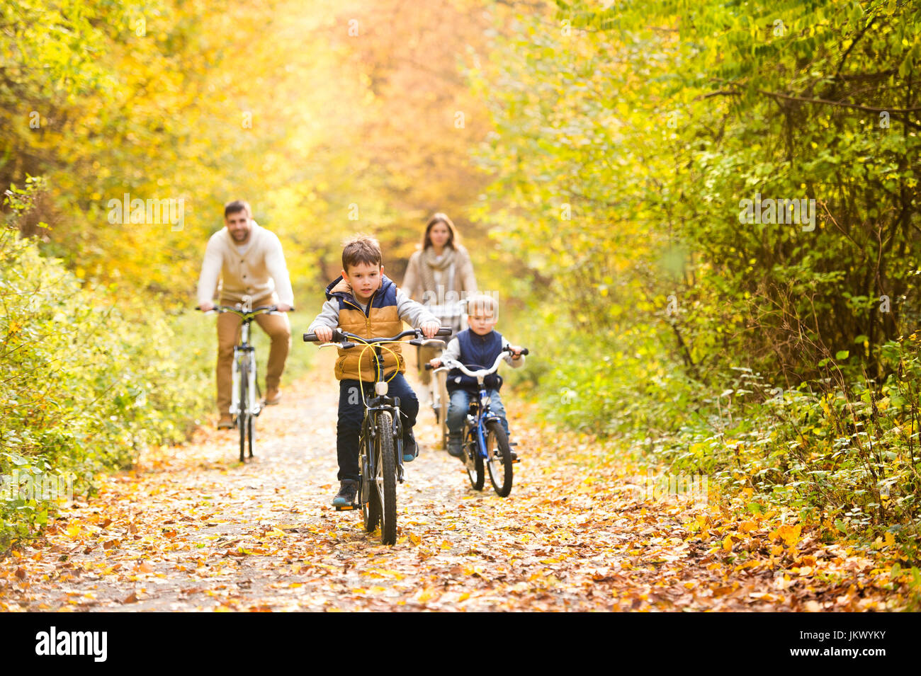 Young family in warm clothes cycling in autumn park - Stock Image