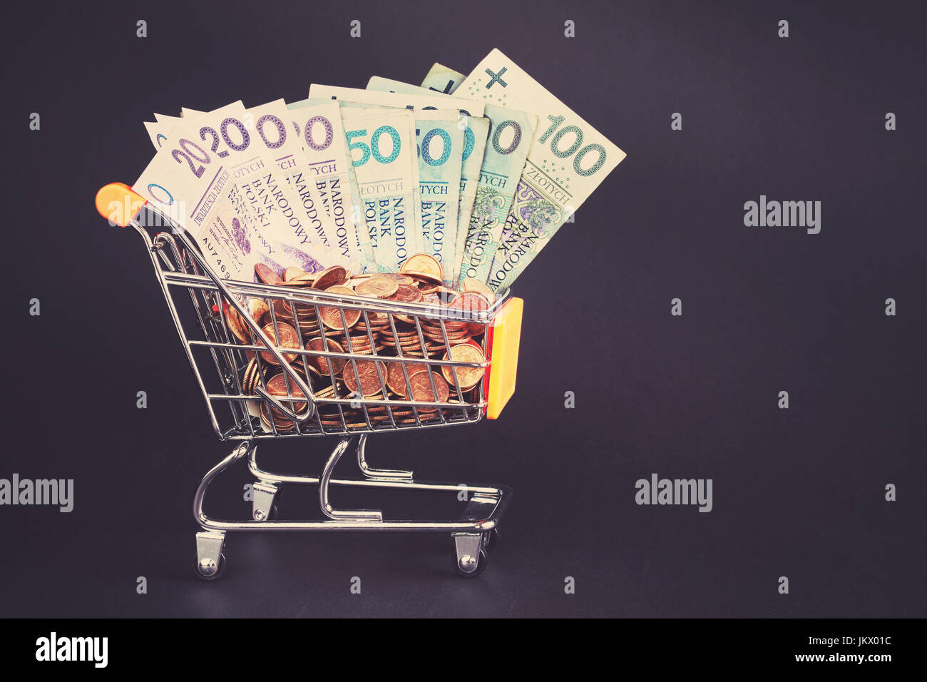Shopping cart filled with polish zloty coins and bills, color toning applied. - Stock Image