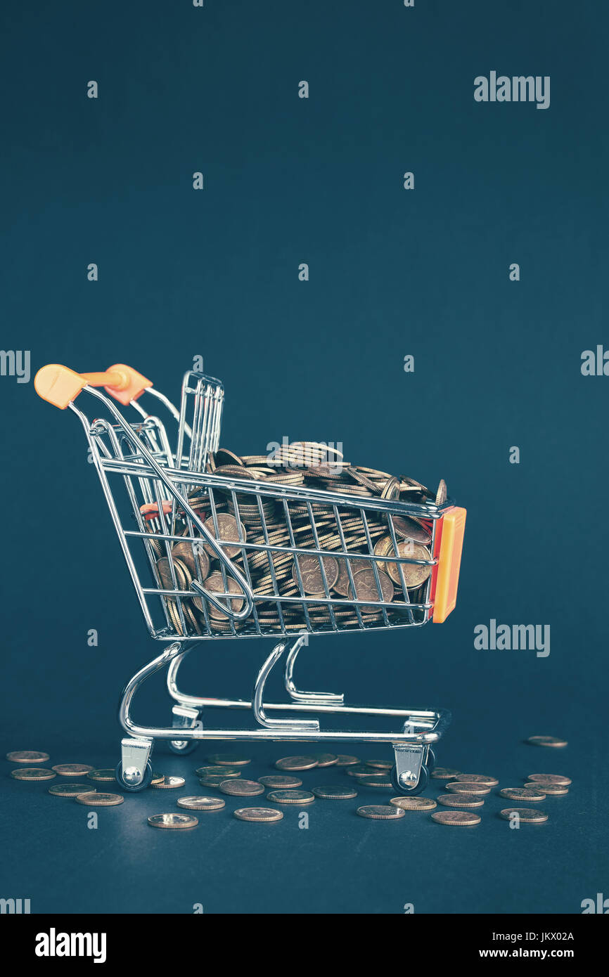Shopping cart filled with golden coins, conceptual picture, color toning applied. - Stock Image