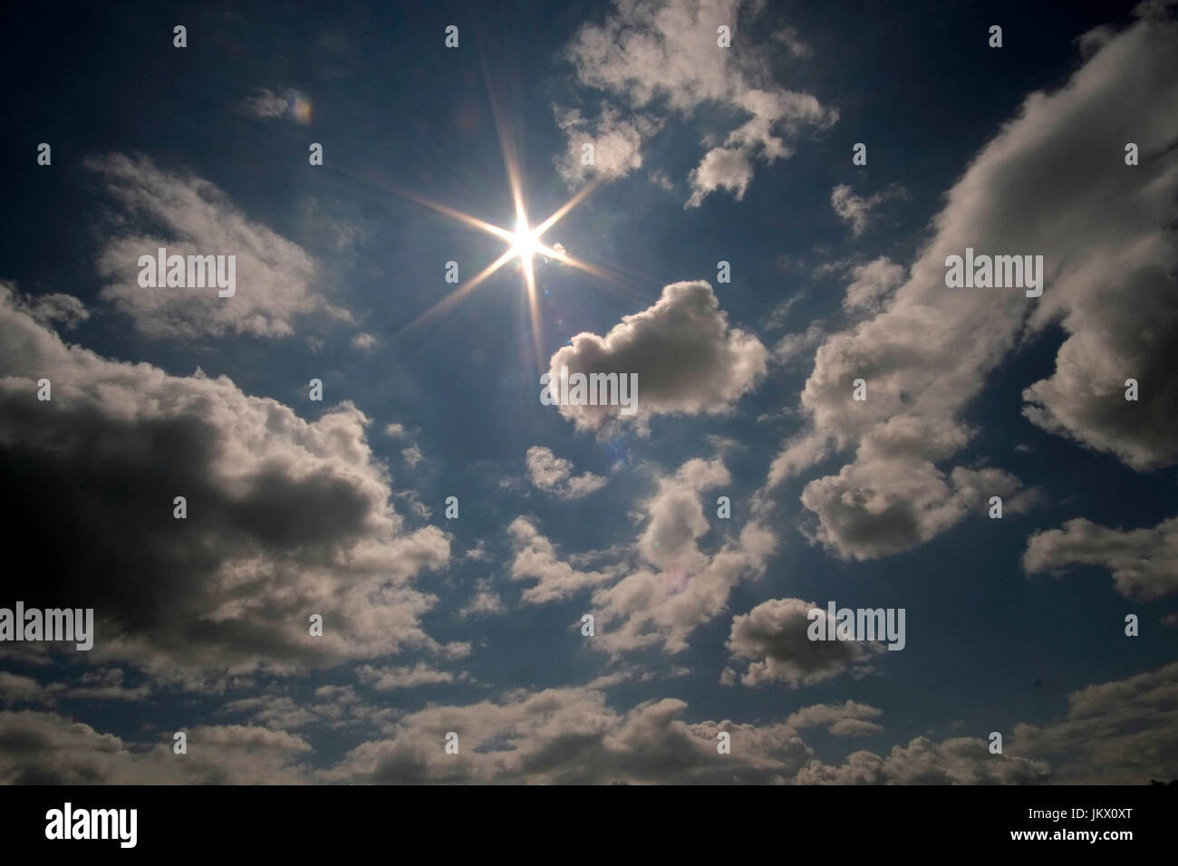 A blue sky with white clouds and a sun starburst. - Stock Image