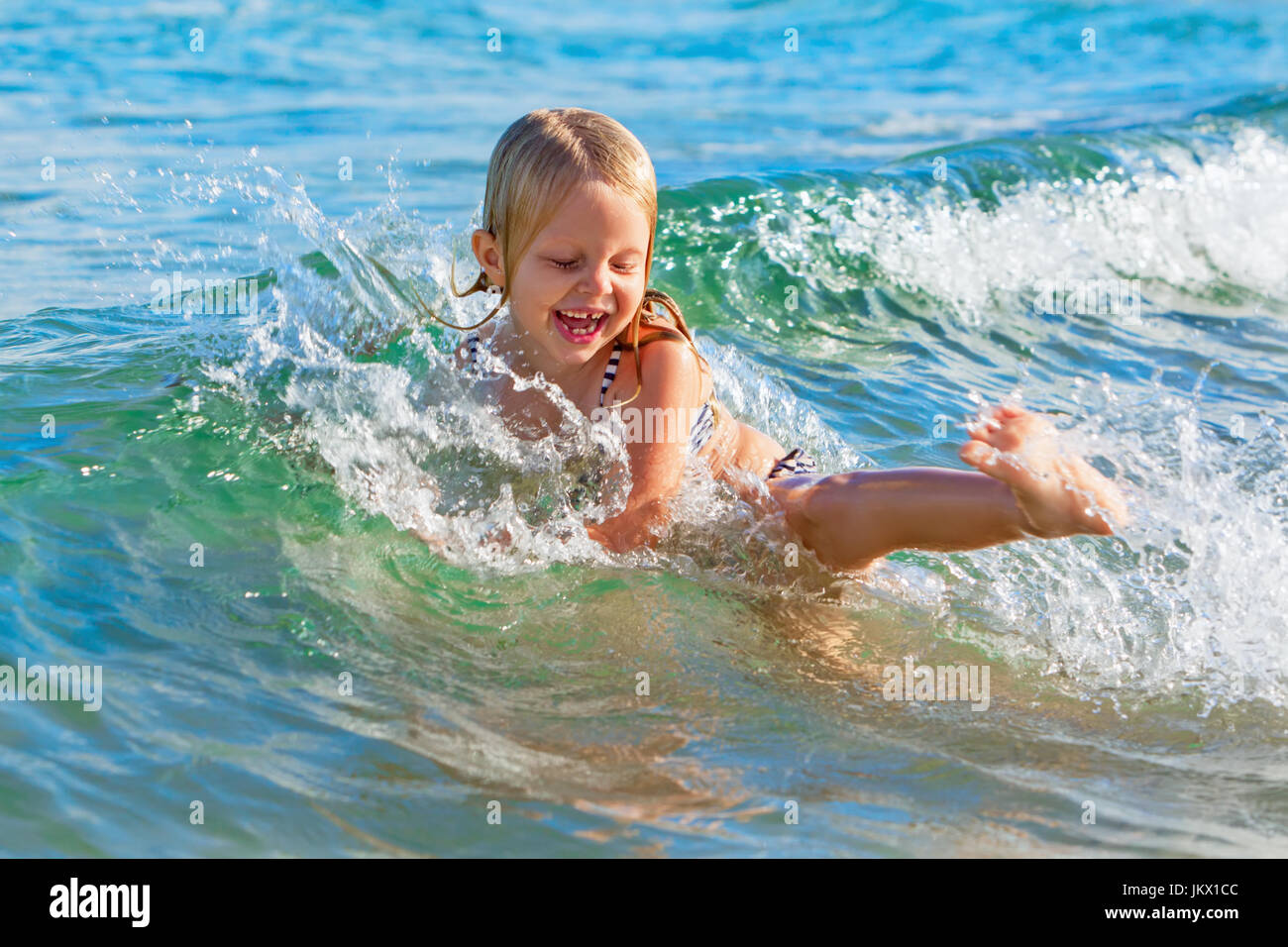 Happy family lifestyle. Baby girl splashing and jumping with fun in breaking waves. Summer travel, water sport outdoor - Stock Image