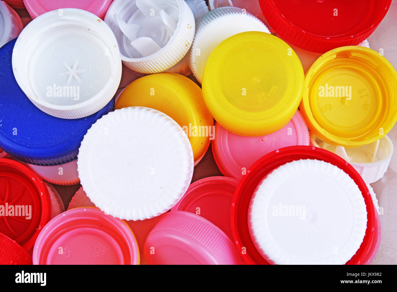 Collect plastic bottle caps.  Close-up shot of stack of recyclable plastic bottle caps on white background. Bottle - Stock Image