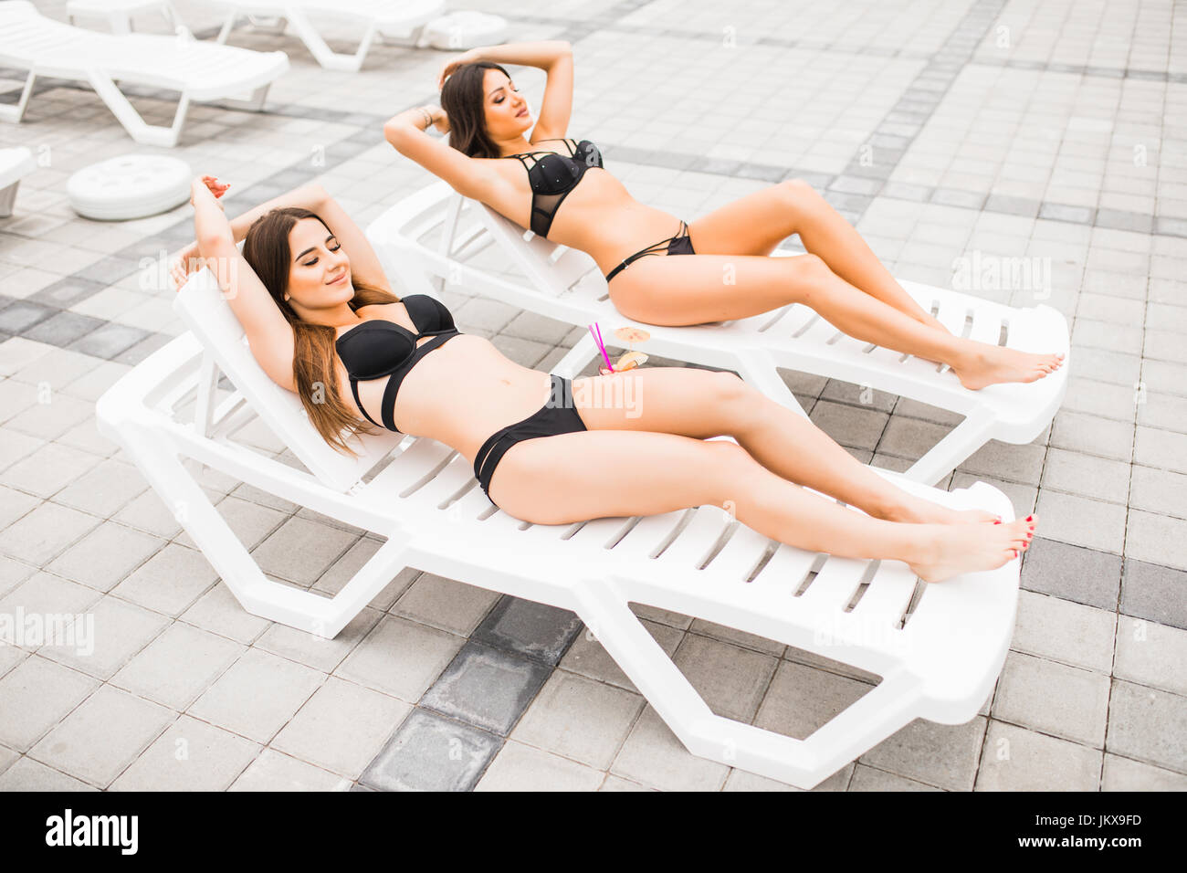 girlfriends clinking glasses with cocktails at the poolside bar - Stock Image