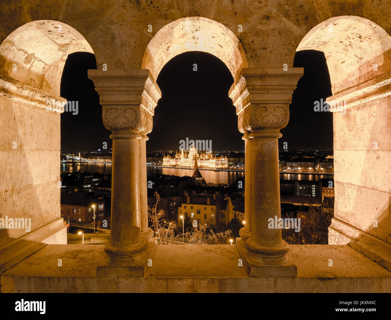 Night view of the famous Hungarian Parliament across the river Danube in Budapest, as seen through the arches of Stock Photo