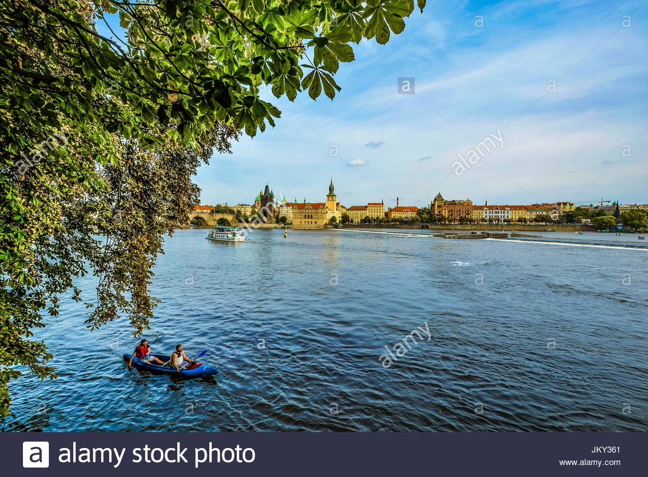 Two men enjoying a ride on the Vltava River in Prague in a blue kayak with the old city in the background on a late - Stock Image