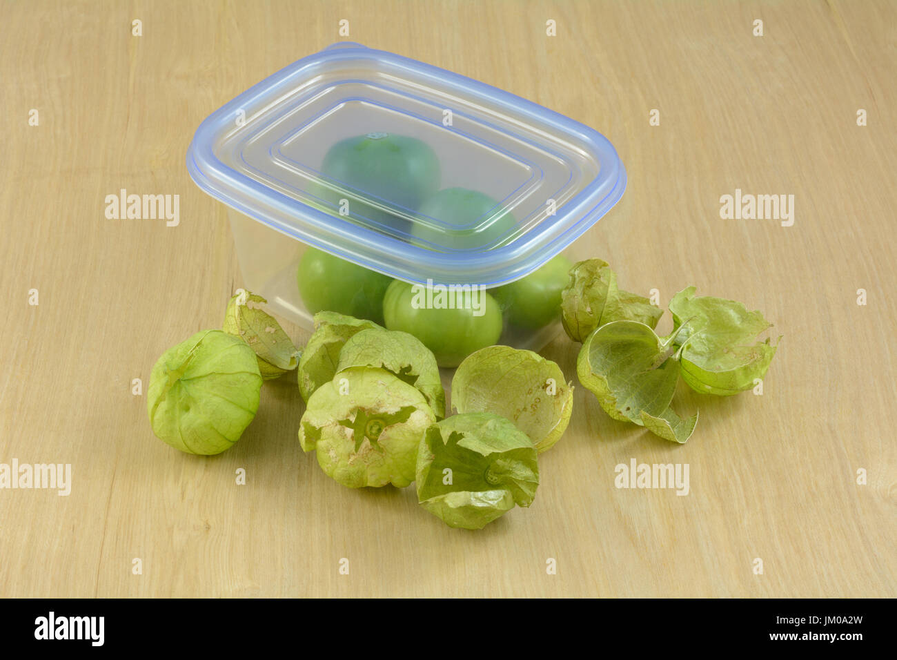 Green tomatillos in husks in plastic refrigerator storage container