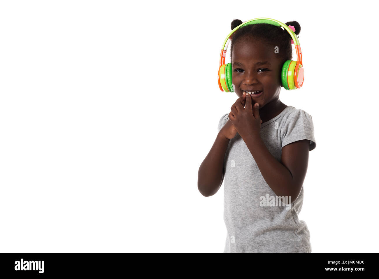 Music and technology concept.African lovely little girl with headphones on white background.Copyspace - Stock Image