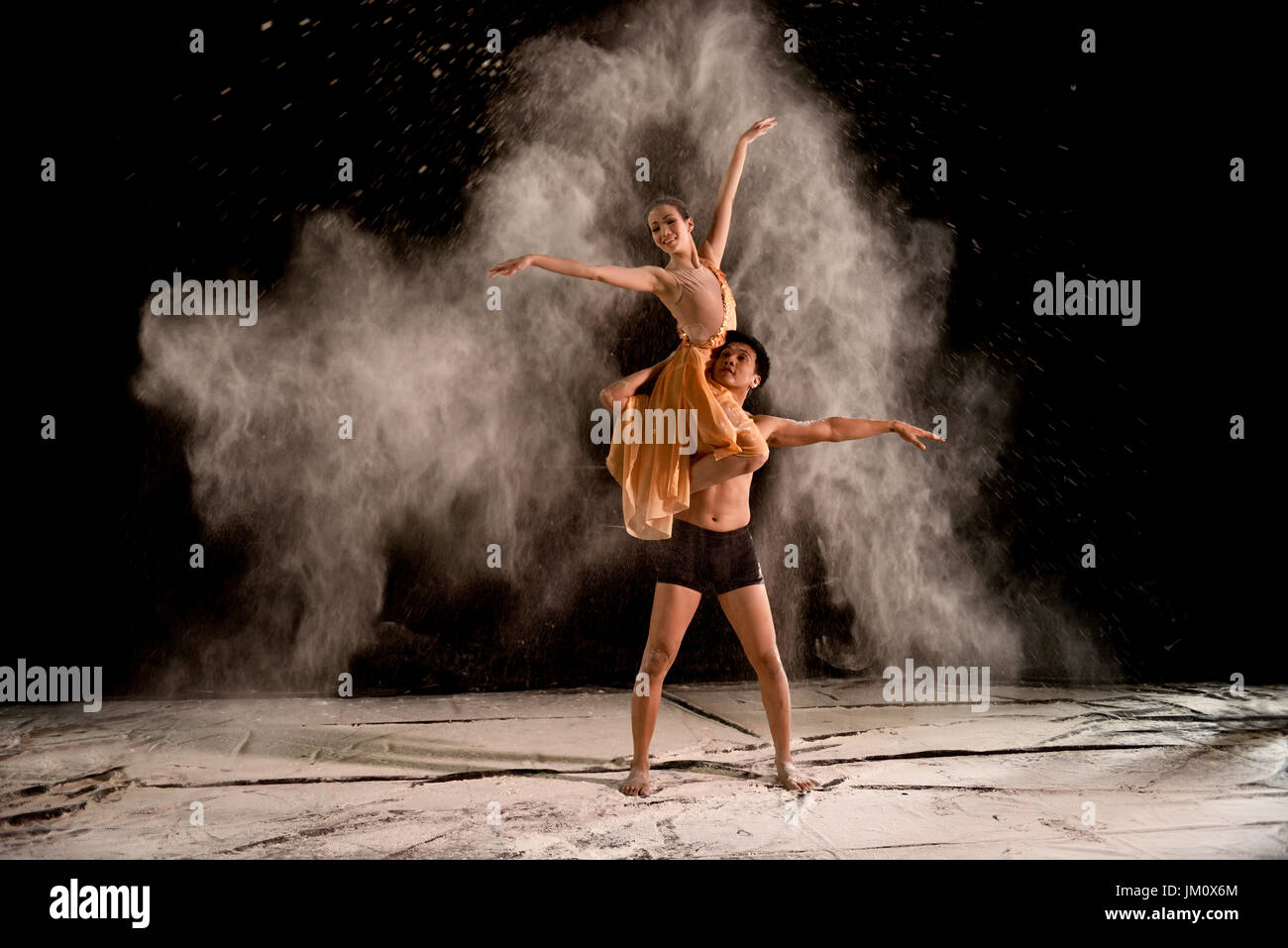 Attractive couple ballet dancer with white powder in the air against black background - Stock Image