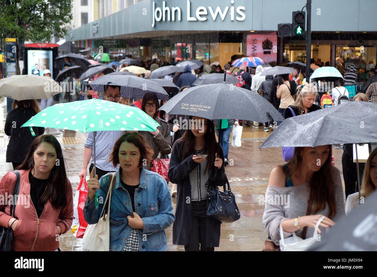 Pix shows: Wet summer in London. Rain battered shopper in Oxford Street near John Lewis store.     Pic by Gavin - Stock Image