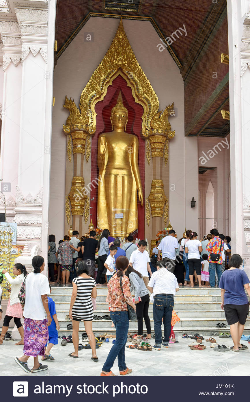 Worshipers at the golden Buddha statute situated at the entrance to Phra Pathom Chedi, the tallest stupa in the - Stock Image