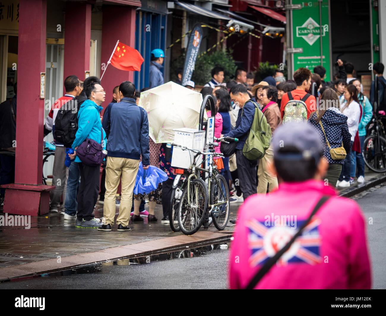 Chinese Tourists Cambridge - Parties of Chinese Tourists with guide with identification flag in the historic centre - Stock Image