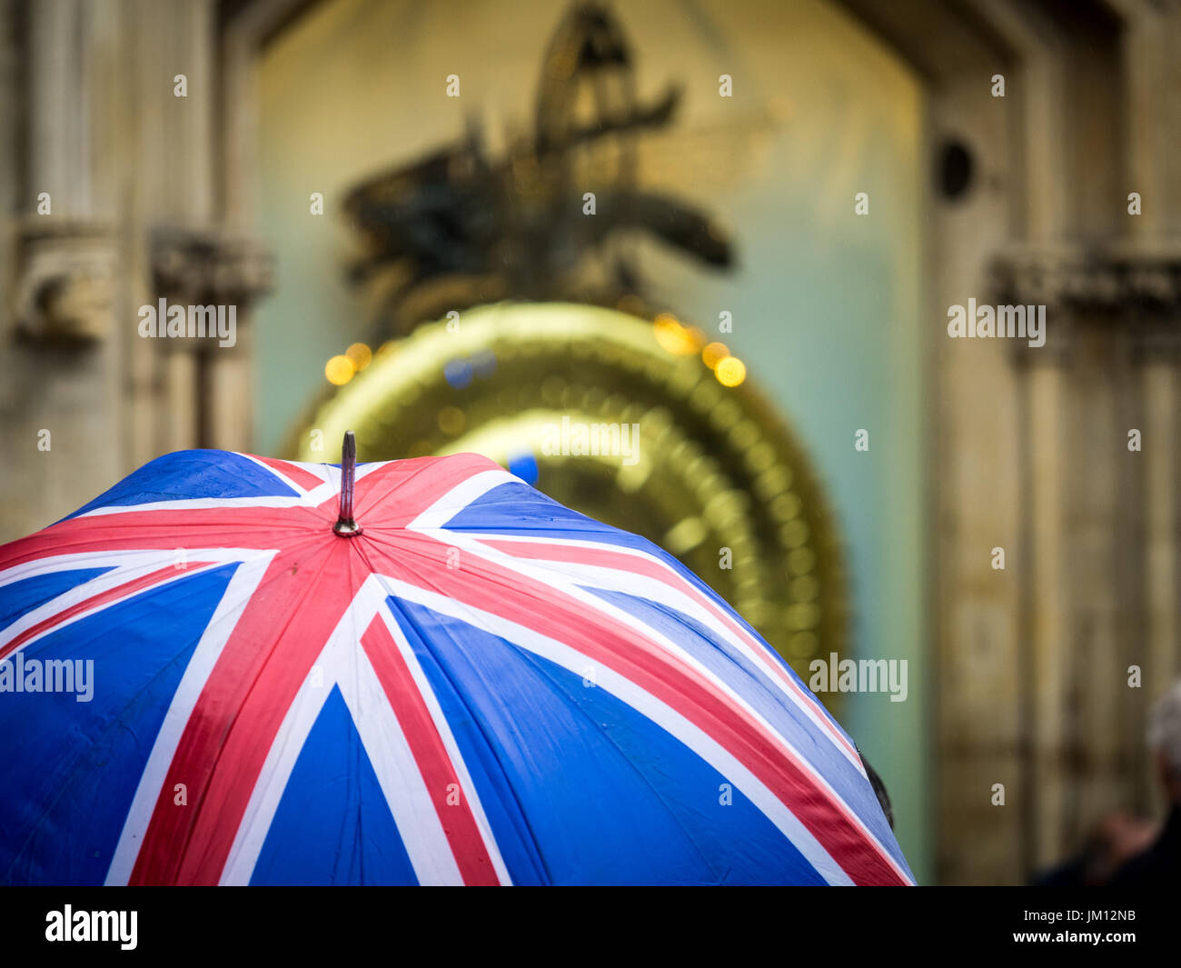 Union Jack Umbrella held by a tourist in front of the Corpus Clock at Corpus Christi College, Cambridge. It was unveilled in 2008 - Stock Image