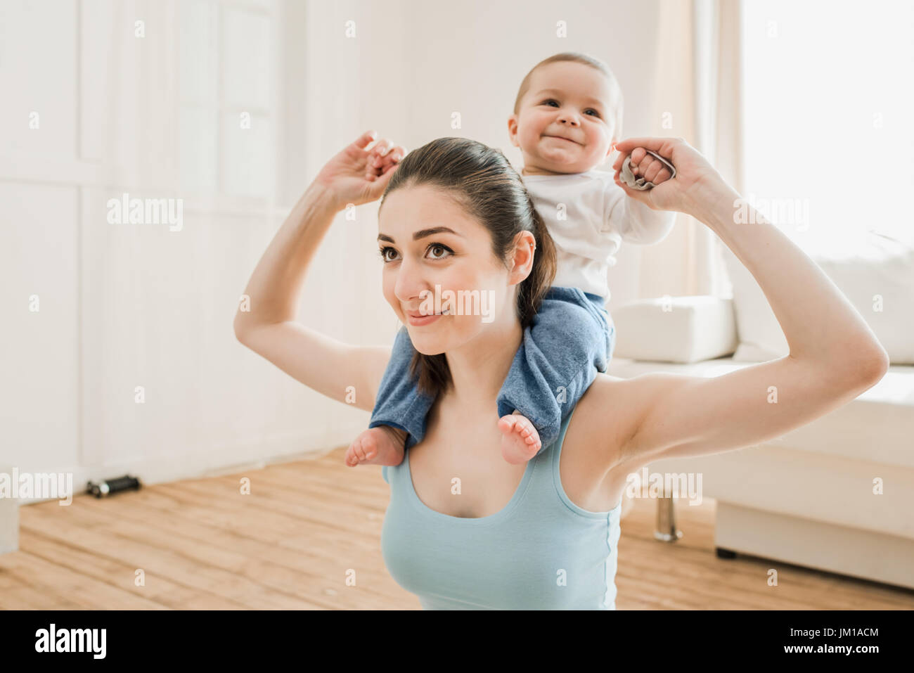 Portrait of young mother carrying her son piggyback at home - Stock Image