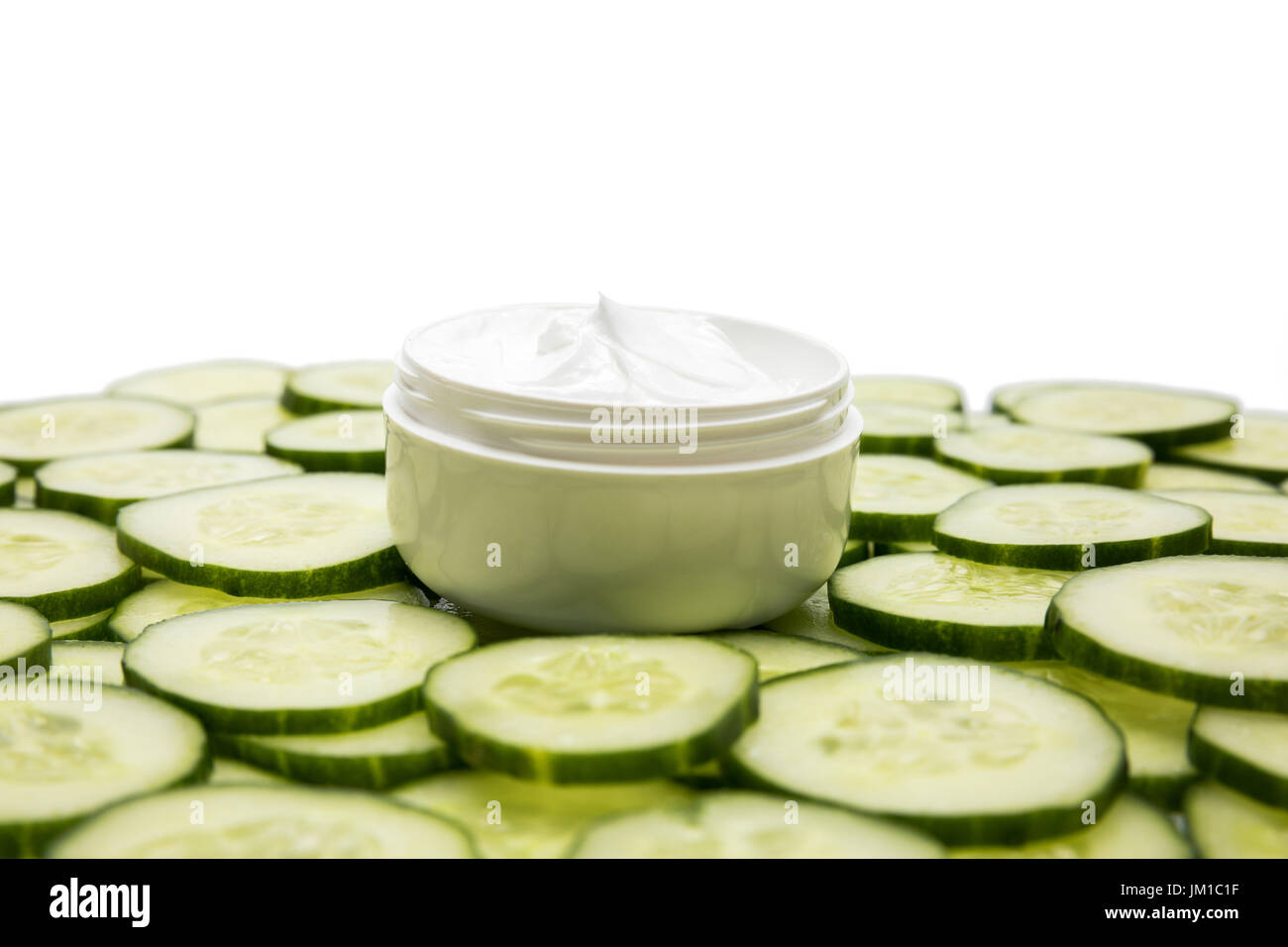 Close-up view of facial cream in container and cucumber slices isolated on white - Stock Image