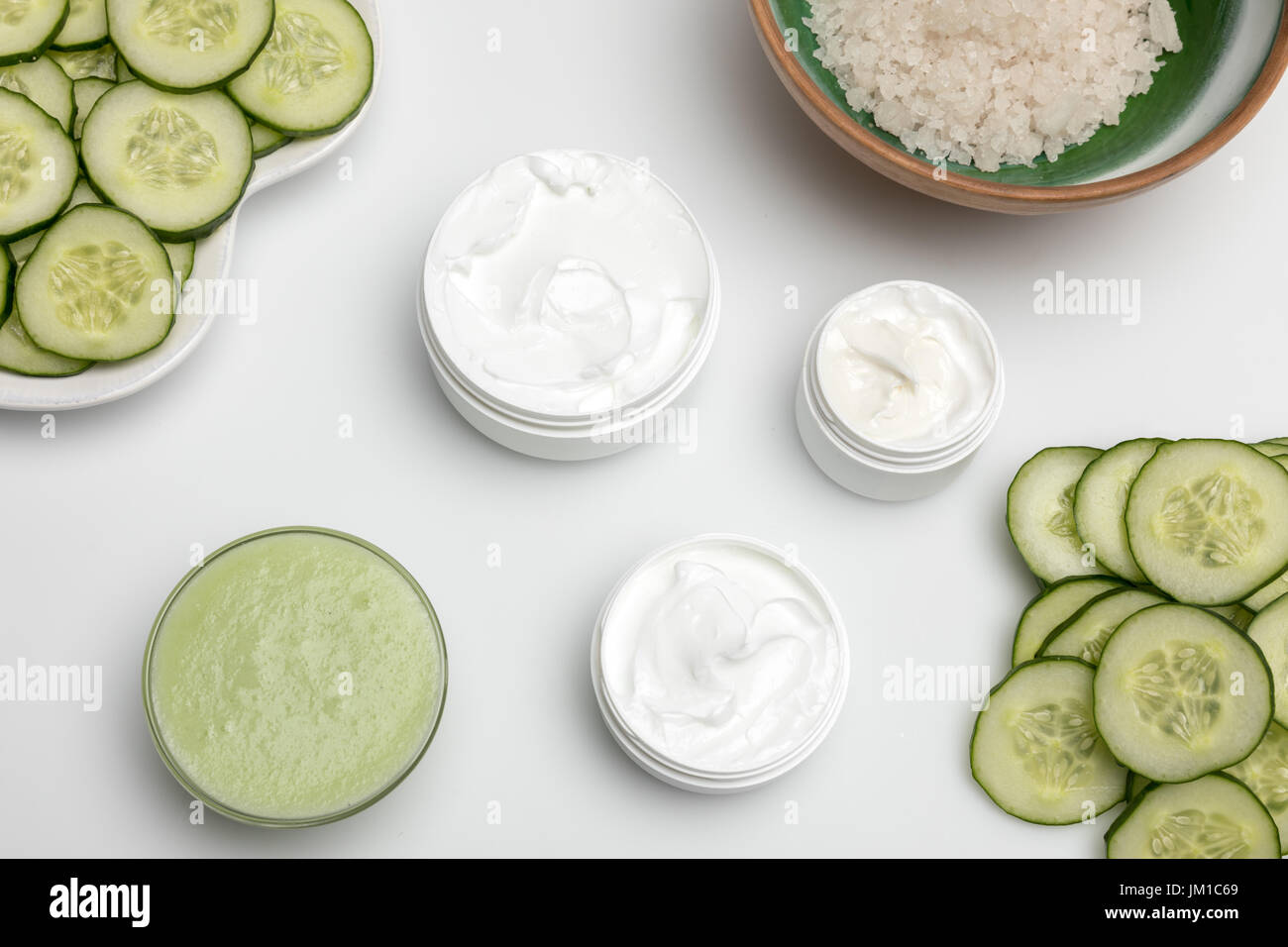 Top view of facial cream in containers and cucumber slices isolated on white - Stock Image