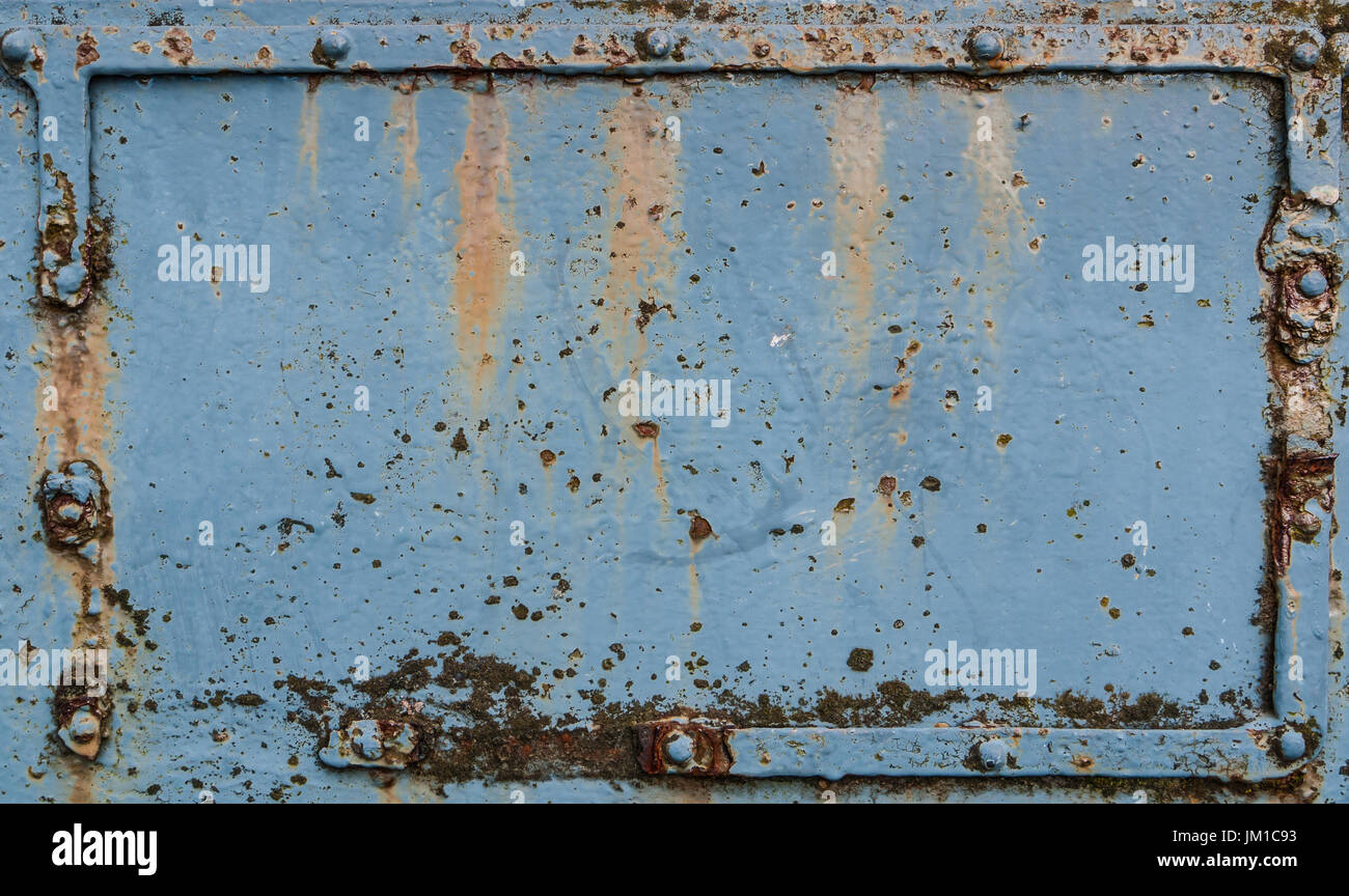 Old blue rusted metal plate with rivets Stock Photo