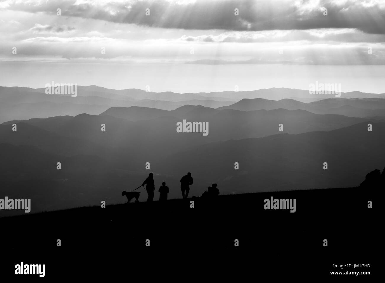 Some people and a dog on top of a mountain, with other mountains and hills in the background, and sunrays coming out of the clouds - Stock Image