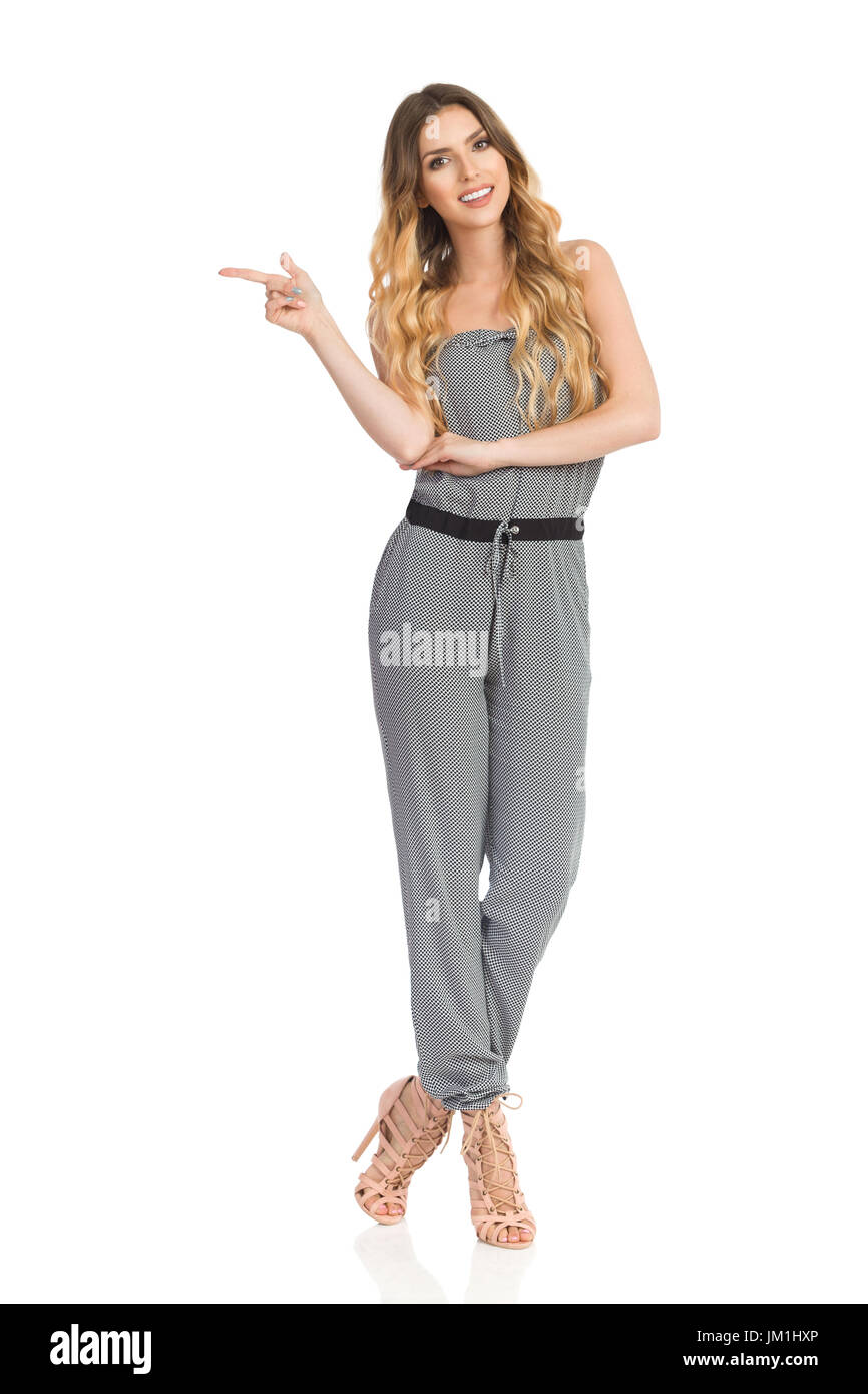 Beautiful young woman in dotted jumpsuit and high heels is standing with legs crossed, looking at camera and pointing. Full length studio shot on isol - Stock Image
