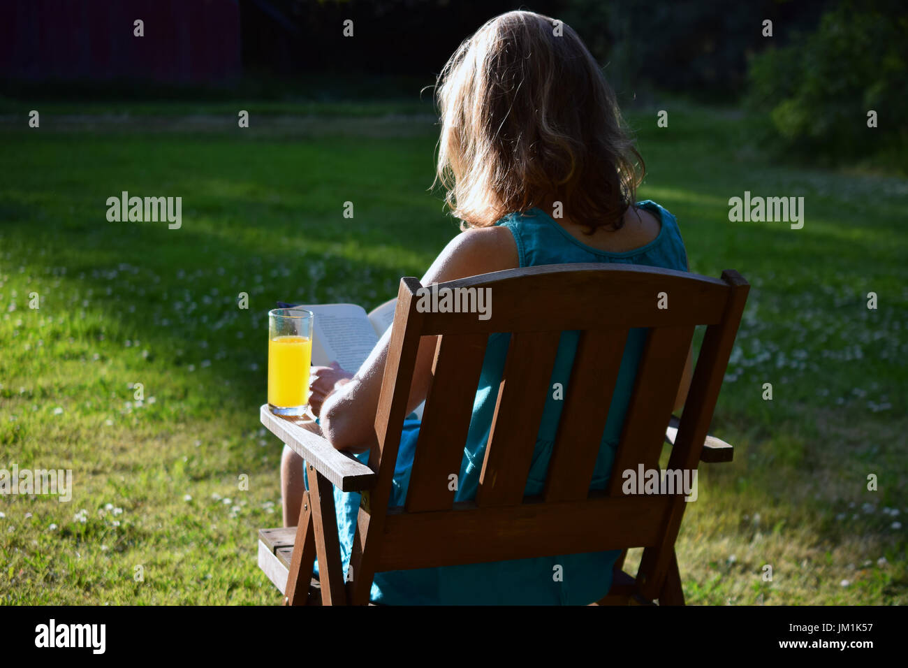 Woman enjoying reading a book and yellow drink in a garden with last rays of evening sunlight on summer. - Stock Image