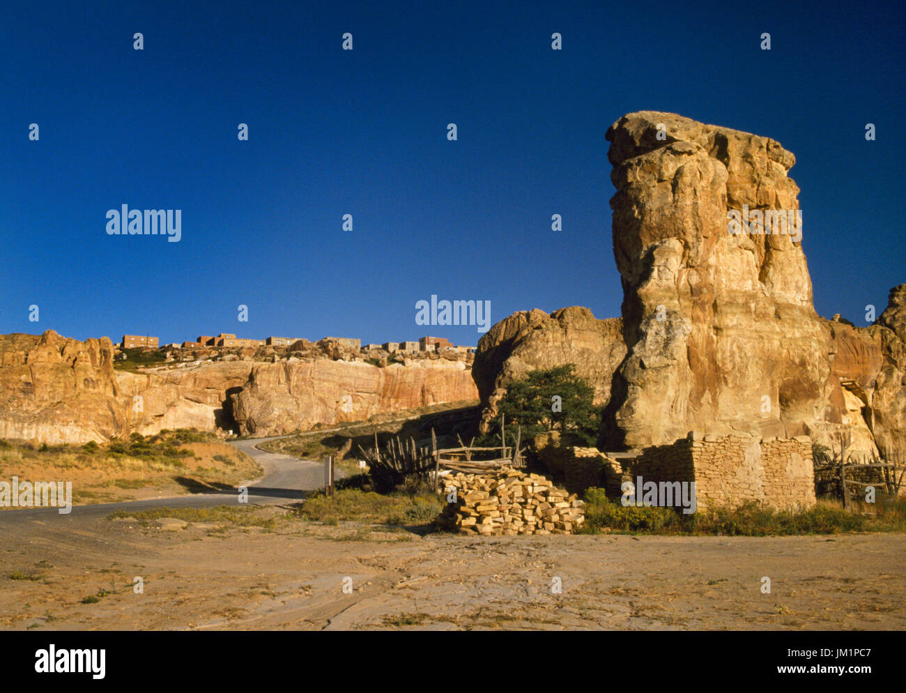 Acoma Pueblo, Grants, New Mexico, USA; rock colums beside modern access road to mesa top and pueblo. Village visible on top of mesa. - Stock Image
