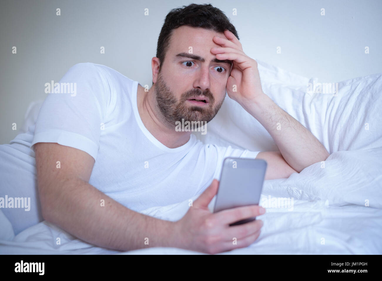 Upset man discovering infidelity affair spying mobile phone - Stock Image