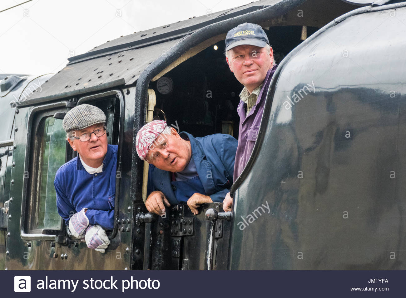 Lancaster Railway Station, UK, 25 July 2017, The Fellsman steam railway tour stops at Lancaster Castle Railway Station to pick up passengers for the steam tour. The crew on the engine footplate wait for the signal from the guard that the train is ready to depart - Stock Image