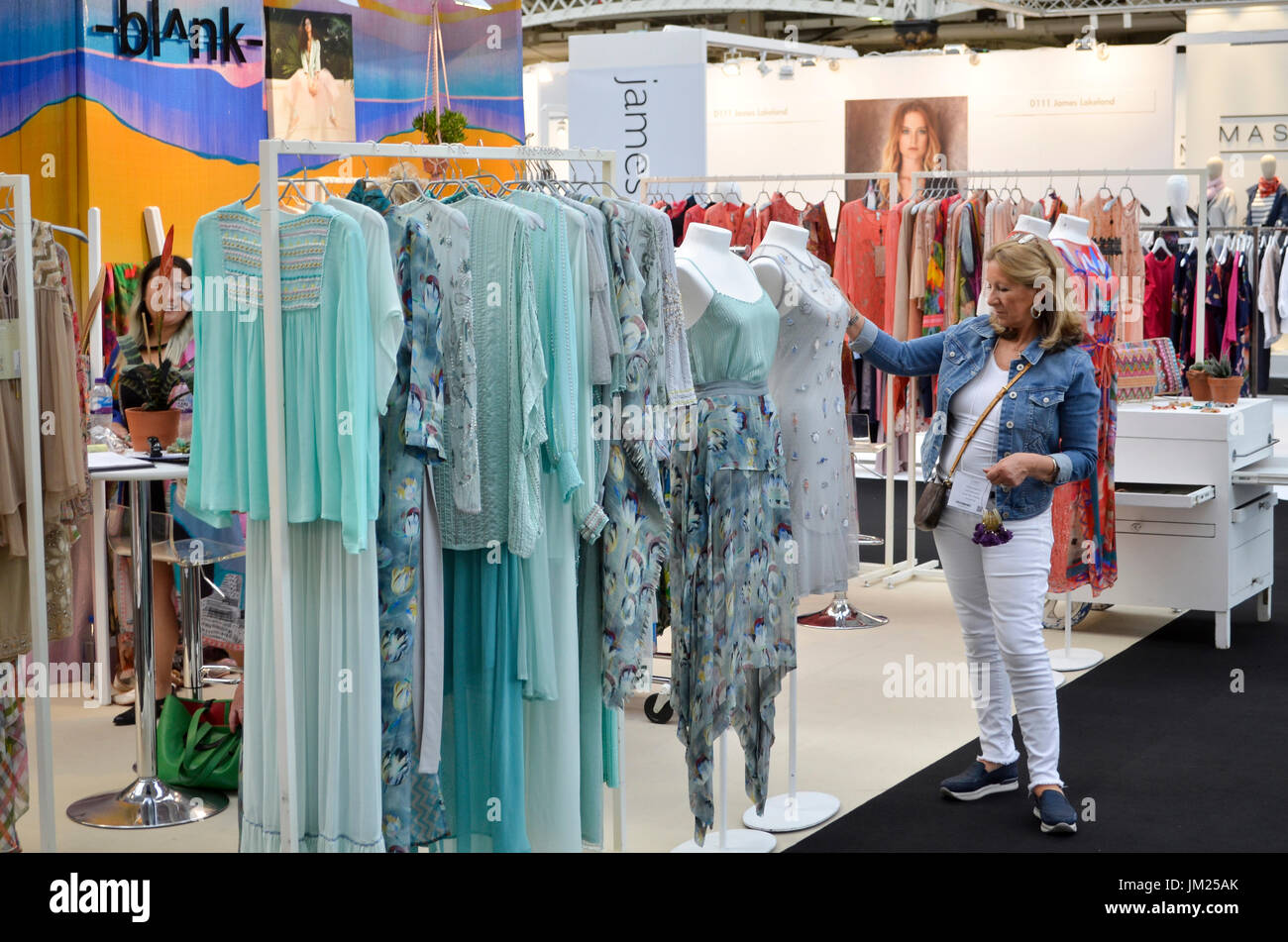 Trade Stands Olympia : Fashion buyer browses the clothing stands at pure london olympia