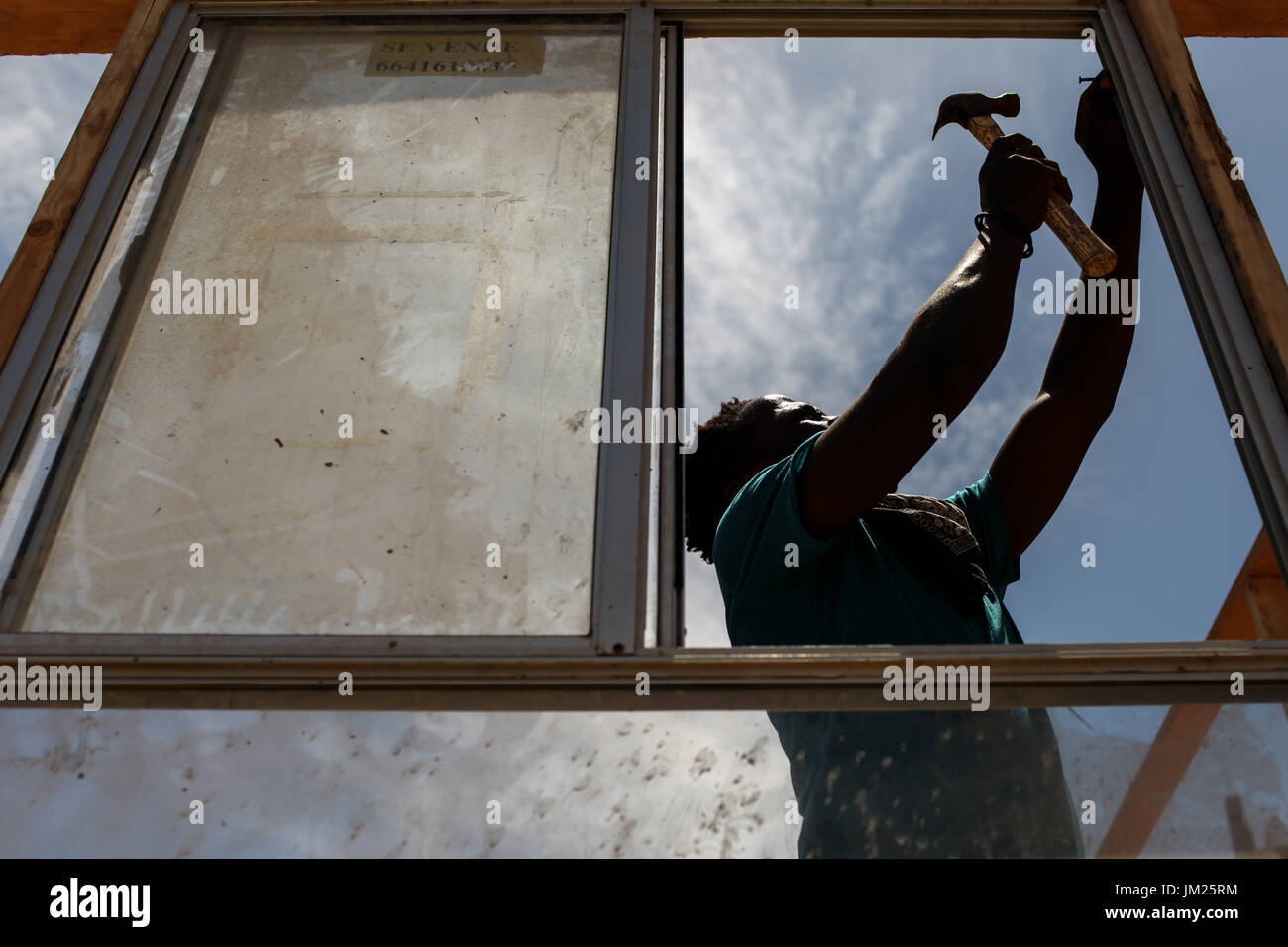 Tijuana, Baja California, Mexico. 19th July, 2017. A Haitian migrant installs a window of a structure along a dry Stock Photo