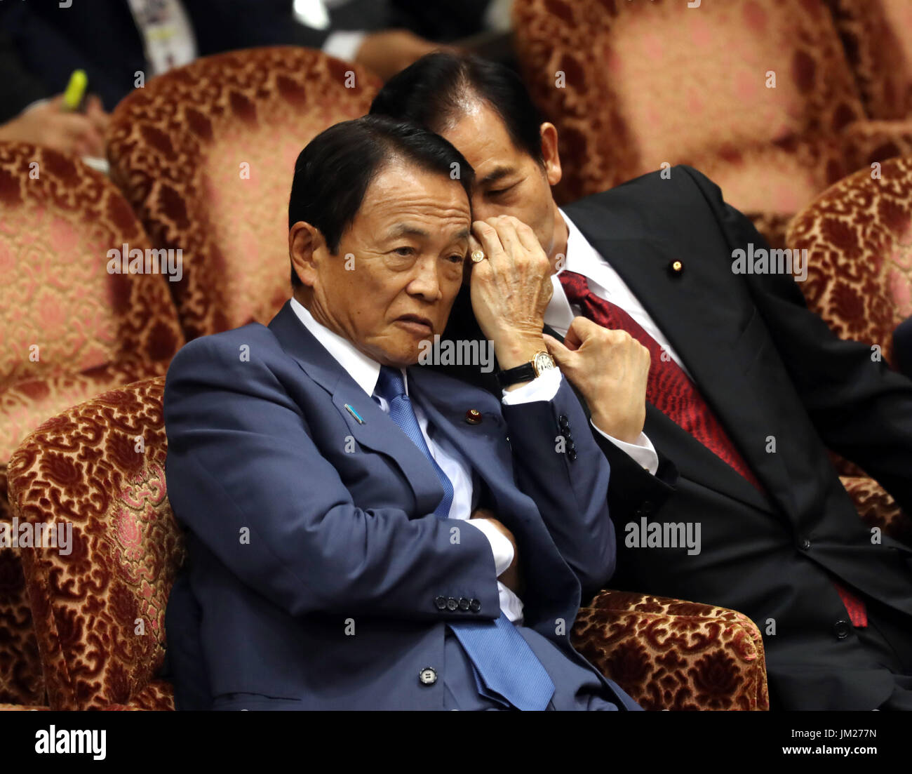 Tokyo, Japan. 25th July, 2017. Japanese Finance Minister Taro Aso (L) chats with Regional Revitalization Minister Kozo Yamamoto at Upper House's budget committee session at the National Diet in Tokyo on Tuesday, July 25, 2017. Abe said he was not asked by his friend Kotaro Kake for help in opening a new university department in Imabari. Credit: Yoshio Tsunoda/AFLO/Alamy Live News - Stock Image