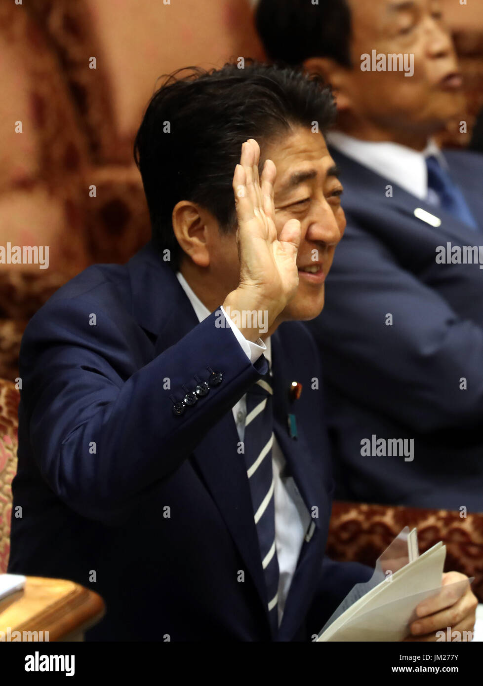 Tokyo, Japan. 25th July, 2017. Japanese Prime Minister Shinzo Abe raises his hand to answer a question by an opposition lawmaker at Upper House's budget committee session at the National Diet in Tokyo on Tuesday, July 25, 2017. Abe said he was not asked by his friend Kotaro Kake for help in opening a new university department in Imabari. Credit: Yoshio Tsunoda/AFLO/Alamy Live News - Stock Image
