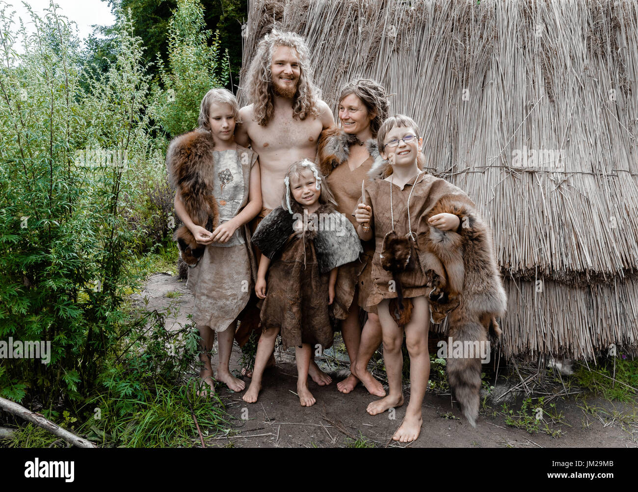 Albersdorf, Germany. 24th July, 2017. Roni and Sofie from Norway and their children Roo, Soini and Tuuli posing outside of their reed hut in the Stone Age Park Dithmarschen in Albersdorf, Germany, 24 July 2017. They are living together under paleolithic, mesolithic and neolithic conditions as part of a live experiment taking place between 24 and 30 July. Photo: Markus Scholz/dpa/Alamy Live News - Stock Image