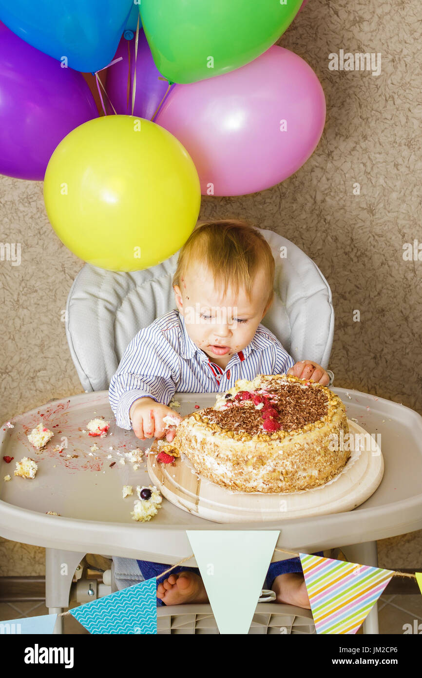 One year old boy is sitting in high chair and tasting his cake. First Birthday celebrating concept. Cake smash Stock Photo
