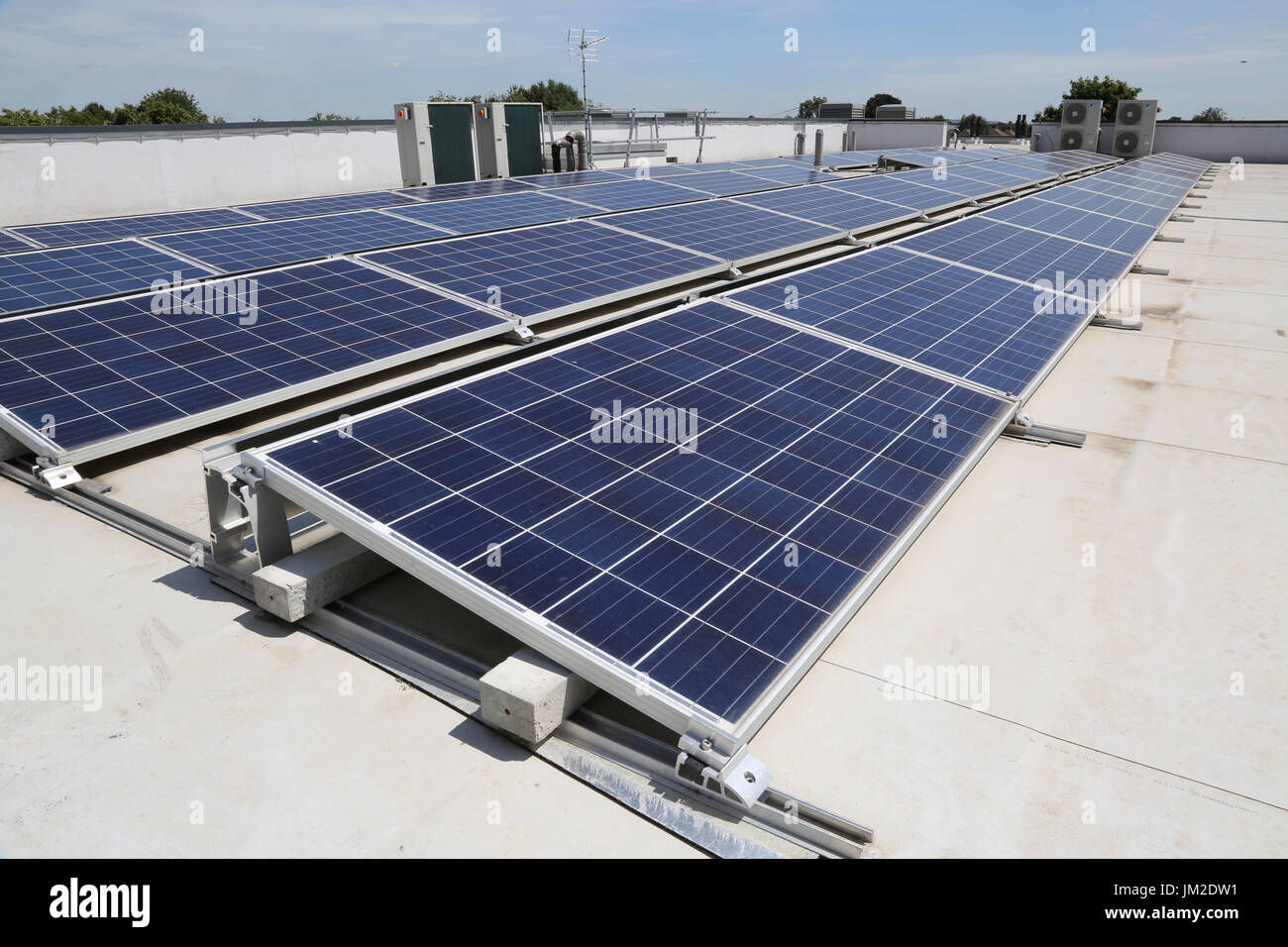 PV solar panels on the flat roof of a new primary school in Essex, UK Stock Photo