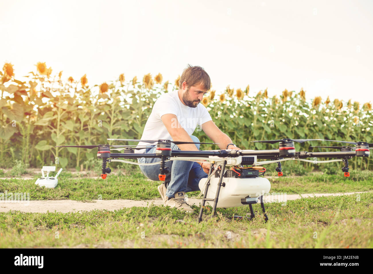 Preparing a drone for take off despite the sunset. - Stock Image