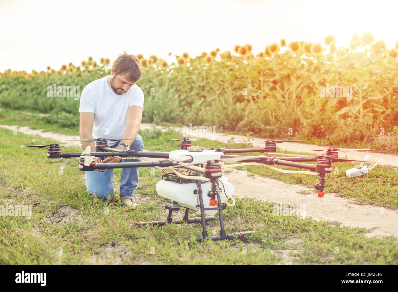 Young engineer preparing agriculture drone before flying - Stock Image