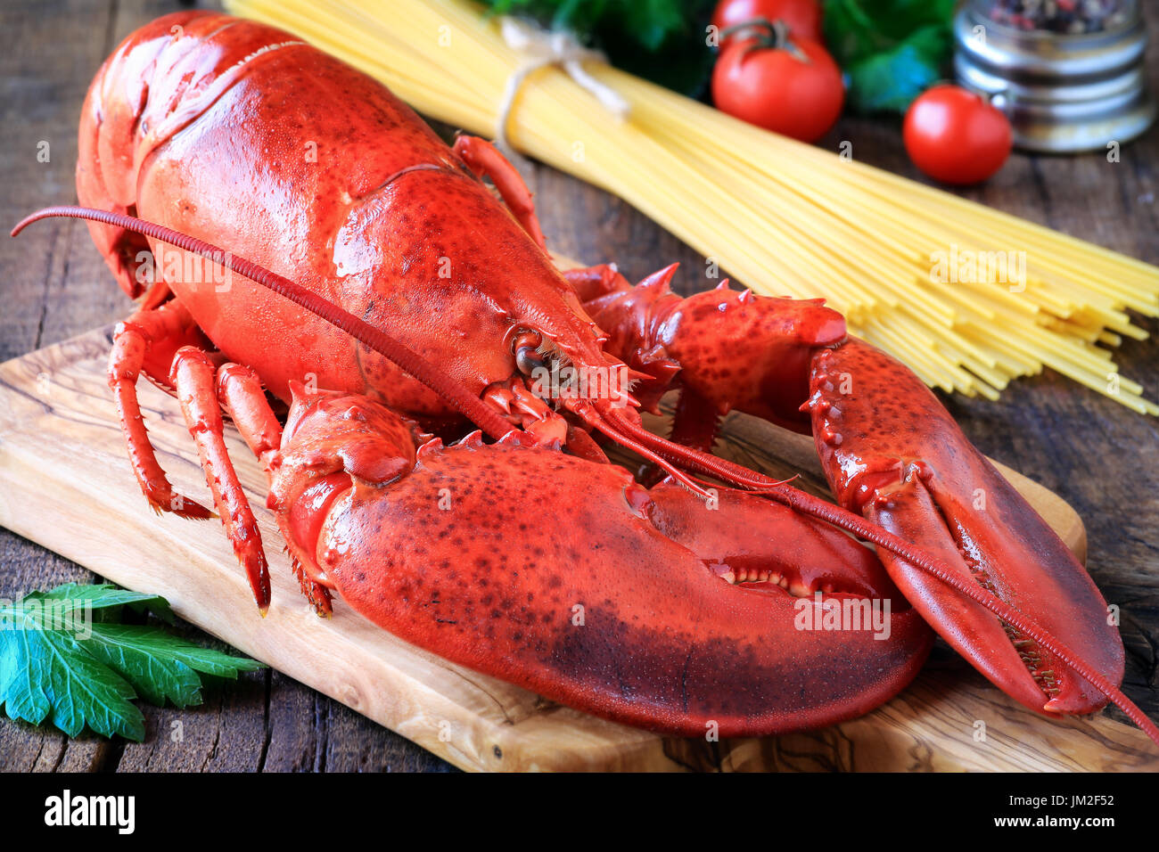 Delicious cooked lobster on wooden cutting board as a concept of Christmas cooking with a candle and fir or pine branches at the  background - Stock Image