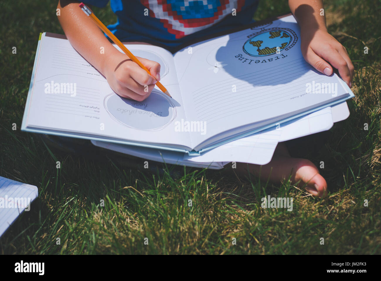 A youth writes in a notebook for school education learning back to school. - Stock Image