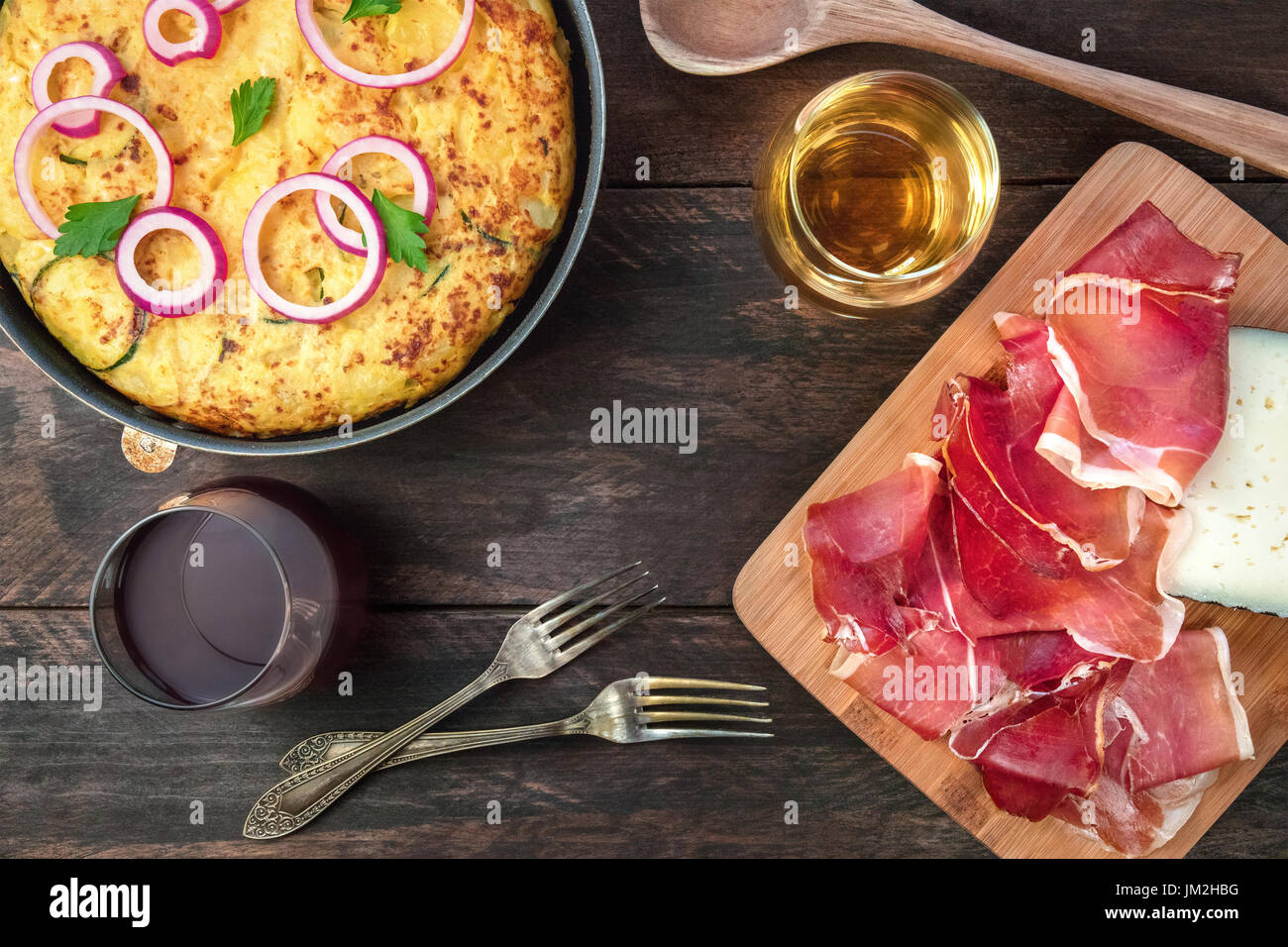 Spanish tortilla in tortillera, with wine, jamon, and cheese - Stock Image