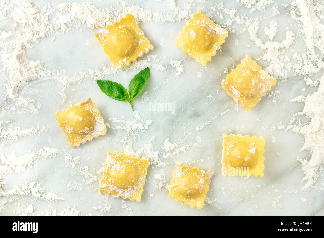 Overhead photo of ravioli with flour and basil leaves - Stock Image