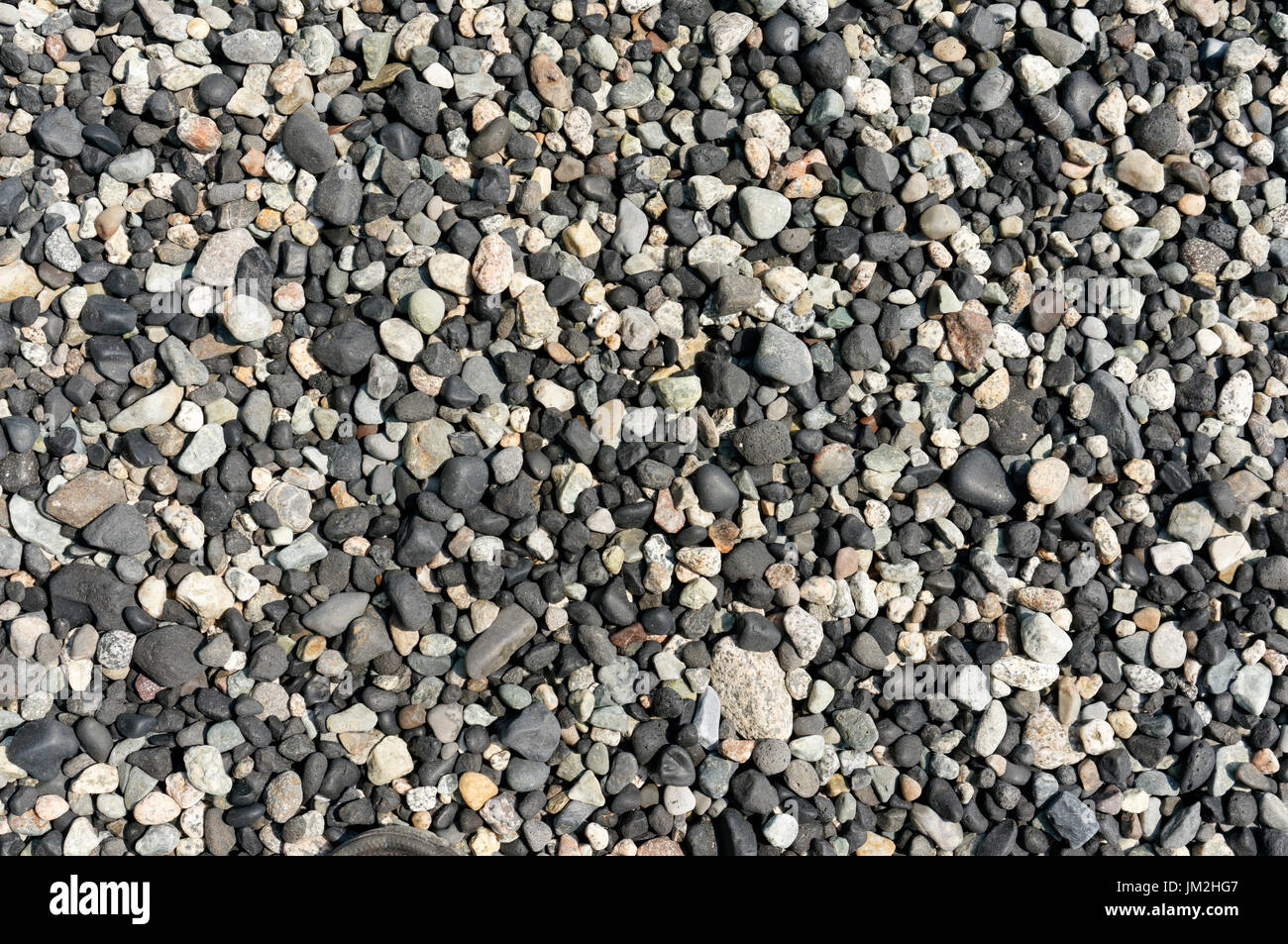 Close-up of multicolored rounded beach pebbles on a rocky beach on Bowen Island, British Columbia, Canada - Stock Image
