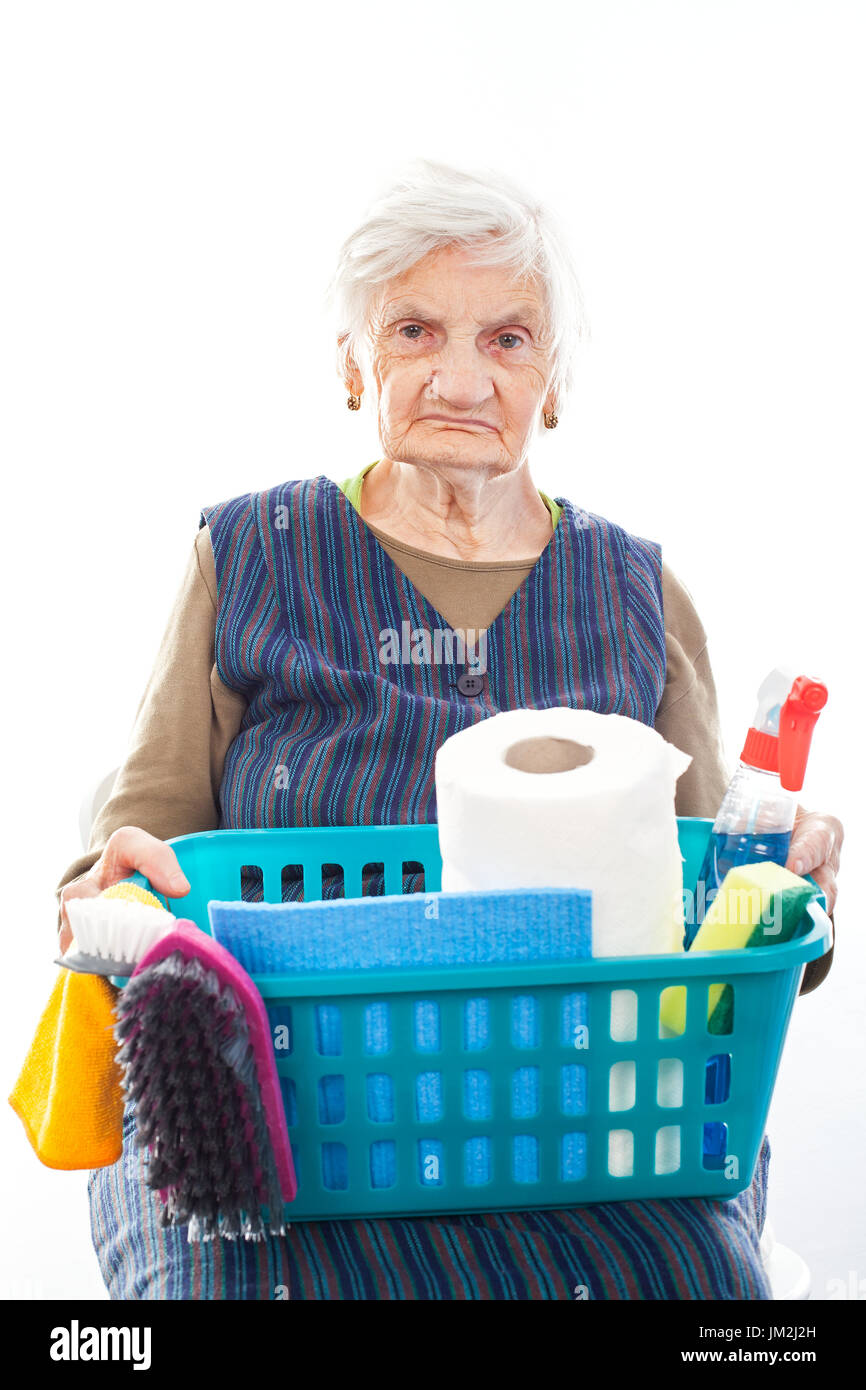 Portrait of a happy senior lady doing housework holding cleaning equipment - Stock Image