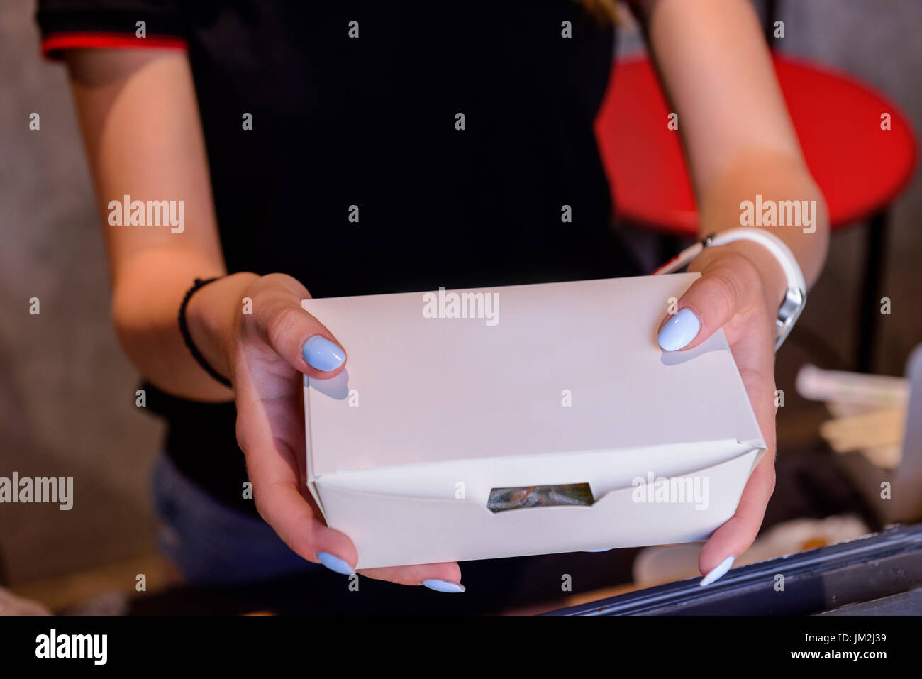 Close up female hands holding and giving take out food in white paper box through the window of issuing orders. Selective focus. Street food concept. - Stock Image