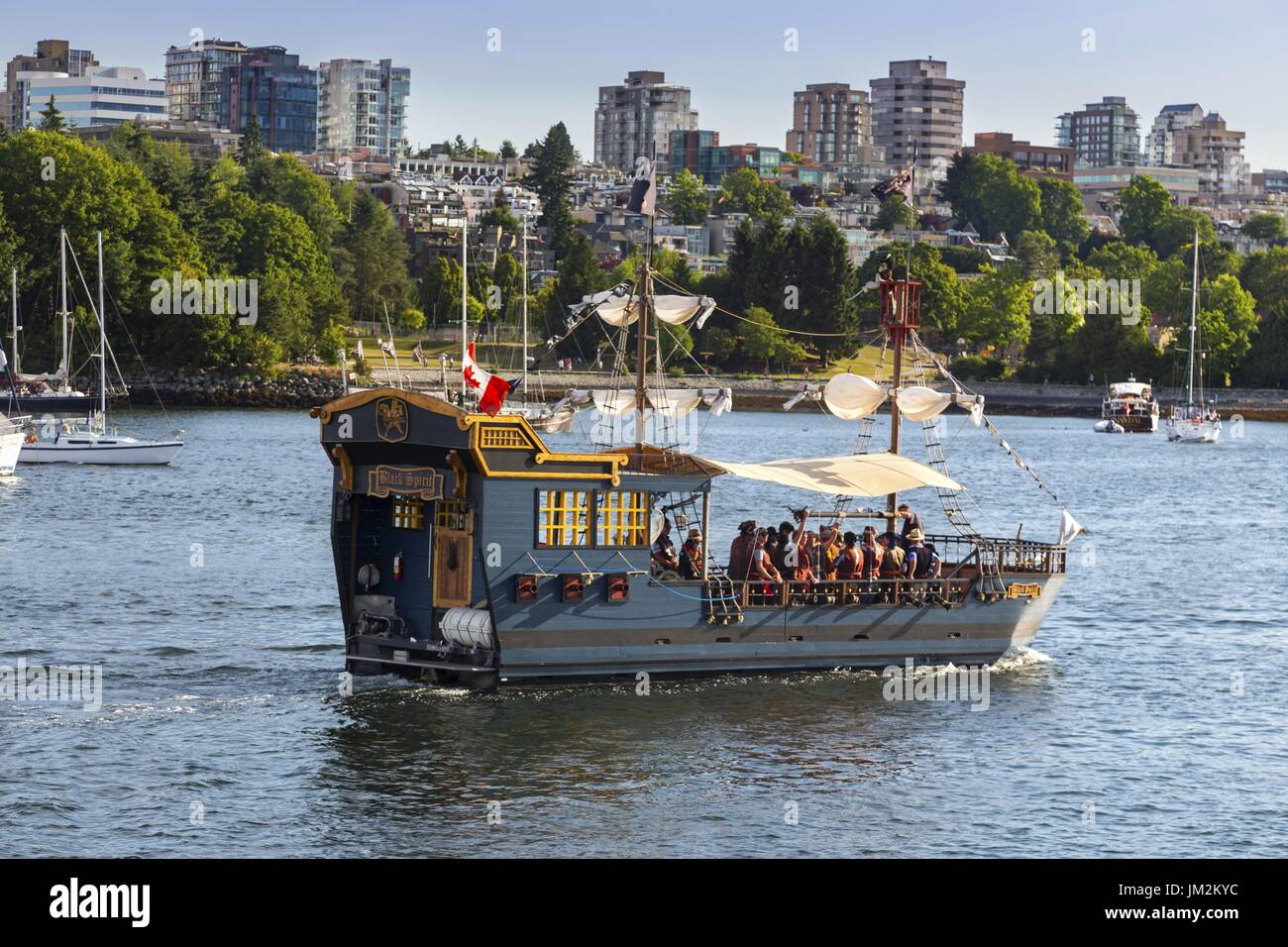 Black Spirit Pirate Cruise Ship with tourists sailing in False Creek across Granville Island Seawall in Vancouver Stock Photo