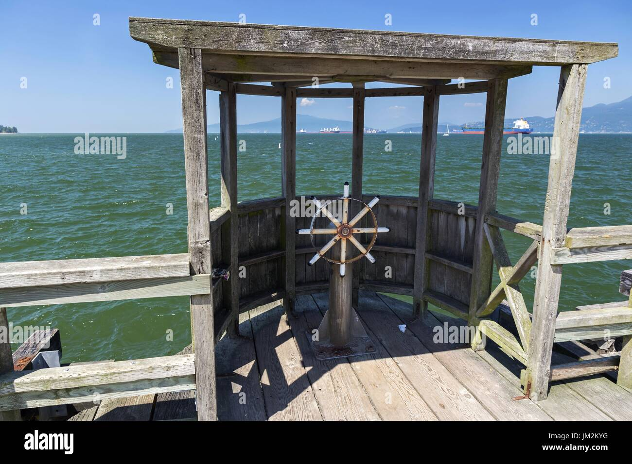 Ship Wheel and Wooden Quay Structure on Jericho Pier with view of Burrard Inlet near University of British Columbia in Vancouver BC Canada - Stock Image