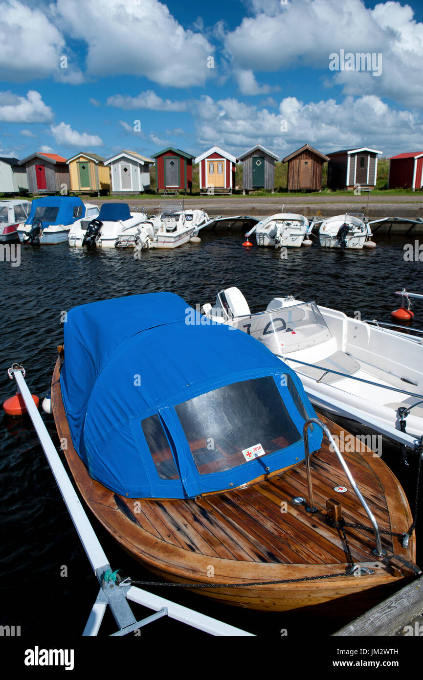 Colourful wooden beach huts and small harbour, Norrebro Hamn, Skane, Sweden - Stock Image